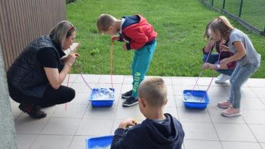 Zdjęcie przedstawia trójkę dzieci i instruktorkę podczas ćwiczeń.