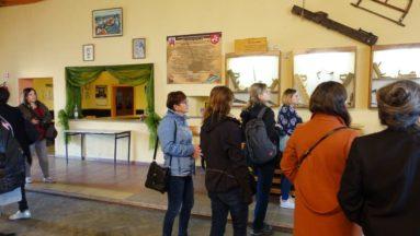 Zdjęcie grupy osób oglądających gabloty z tradycyjnymi narzędziami stolarskimi