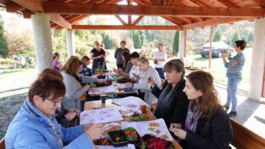 Zdjęcie grupy siedzącej przy stole i malującej kwiatami wzory na torbach