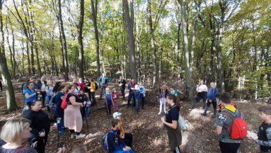 grupa osób i harcerzy w lesie