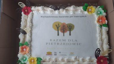 Tort ze zdjęciem logotypu Stowarzyszenia Razem dla Pietrzejowic oraz Działaj Lokalnie z napisem Międzypokoleniowa Kawiarenka gier towarzyskich