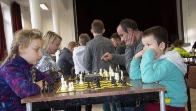 Zdjęcie przedstawia grupę dzieci i dorosłych siedzących przy stołach i grających ze sobą w szachy podczas turnieju.