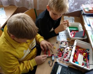 Zdjęcie przedstawia dwójkę dzieci przystole, układających robota zklocków Lego.