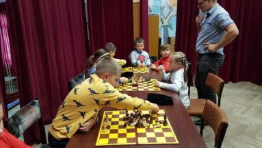 Na zdjęciu grupa dzieci siedi przy stołach na których rozłożone są zestawy szachowe. Obok dzieci stoi nauczyciel.