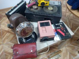Na stoliku przedmioty zczasów PRL-u adapter, projektor, magnetofon kasetowy, płyta wideo, zegar, aparat dozdjęć