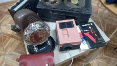 Na stoliku przedmioty z czasów PRL-u adapter, projektor, magnetofon kasetowy, płyta wideo, zegar, aparat do zdjęć