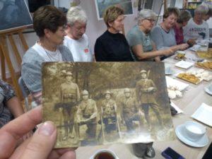 Grupa kobiet przystole oglądających archiwalne zdjęcia, nazdjęciach żołnierze zkarabinami