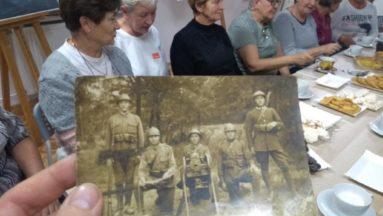 Grupa kobiet przy stole oglądających archiwalne zdjęcia, na zdjęciach żołnierze z karabinami