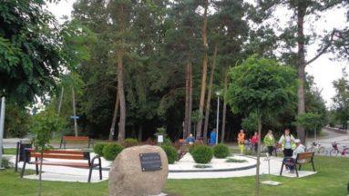 Grupa osób w parku dużo zieleni drzewa, krzewy, ławki, kamień pamiątkowy z tablicą upamiętniającą ofiary wojny