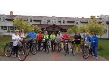 """Grupa uśmiechniętych osób z rowerami  przygotowana do wyjazdu na wycieczkę pn. """"Wolność kocham i rozumiem"""""""