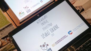 Zdjęcie przedstawia laptopa i rzutnik, na którym wyświetlany jest film promocyjny.