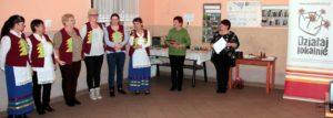 Zdjęcie przedstawia grupę osób we wnętrzu, pozujących dozdjęcia zotrzymanymi dyplomami.