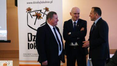 Zdjęcie przedstawia trzech mężczyzn w garniturach, rozmawiających ze sobą. W tle widać rollup z logiem Działaj Lokalnie.