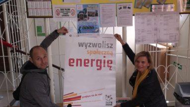 """Zdjęcie przedstawia dwie osoby trzymające plakat Działaj Lokalnie z napisem """"Wyzwolisz społeczną energię""""."""
