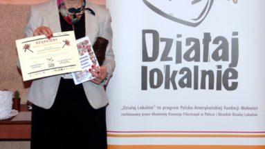 Na zdjęciu wiceburmistrz prezentuje sąsiedzką książkę kucharską i podziękowania dla gminy od organizacji.