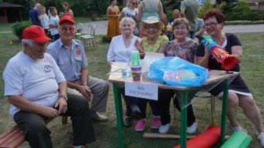 Zdjęcie przedstawia grupę starszych ludzi, siedzących przy stolikach w plenerze.