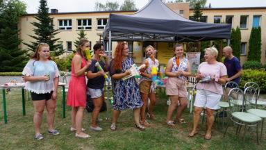 Zdjęcie przedstawia grupę ludzi na imprezie plenerowej.