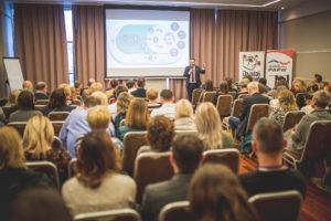 Zdjęcie przedstawia salę wykładową wtrakcie trwania wykładu, wypełnioną ludźmi. Prowadzący omawia slajd oCelach Zrównoważonego Rozwoju.
