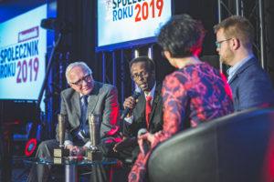 Zdjęcie przedstawia dziennikarkę itrzech laureatów Nagrody podczas rozmowy nascenie.