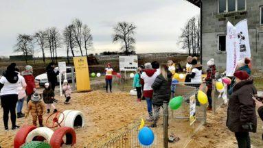 Zdjęcie przedstawia rodziny na nowo otwartym placu zabaw.
