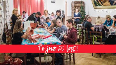 """Zdjęcie przedstawia osoby siedzące przy stolikach podczas spotkania wigilijnego organizowanego w ramach """"Działaj Lokalnie"""". Na zdjęcie nałożony jest napis """"To już 20 lat!""""."""