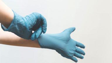 Zdjęcie przedstawia osobę w trakcie zakładania niebieskich gumowych rękawiczek.