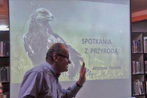 Na zdjęciu widać prelegenta natle prezentacji naktórej znajduje się napis: Spotkania zprzyrodą
