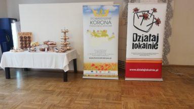 Stół ze słodkościami oraz roll up Stowarzyszenia Korona Północnego Krakowa oraz Działaj Lokalnie