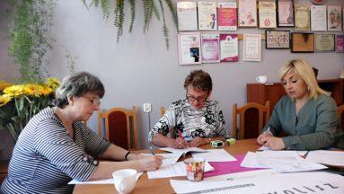 Na zdjęciu osoby przy biurku podpisują umowy.