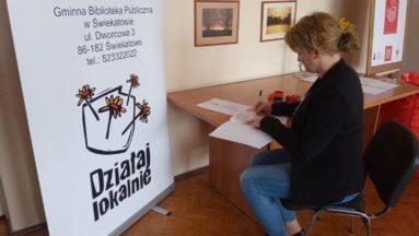 Zdjęcie przedstawia osobę przy biurku, obok banera Działaj Lokalnie, podpisującą umowę.