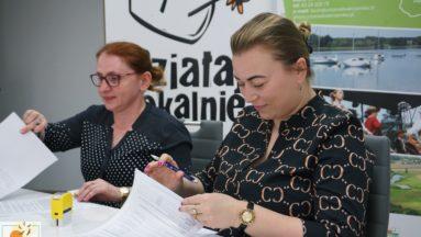 Zdjęcie przedstawia osoby podczas podpisywania umów.