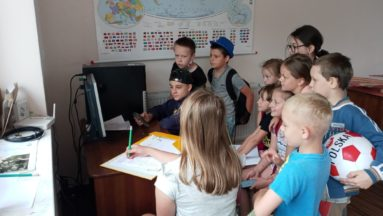 Zdjęcie przedstawia grupę dzieci przed komputerem.