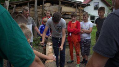 Uczestnicy projektu sprawdzają swoje siły w heblowaniu drzewa, które będzie wykorzystane do budowy pojazdu Flinstonów.