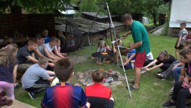Młodzież piecze kiełbaski nad ogniskiem. Dla młodszych uczestników kiełbaski są pieczone na ruszcie.