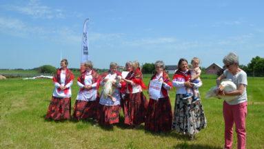 Zdjęcie przedstawia grupę osób w plenerze, ubraną w tradycyjne stroje.