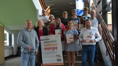 """Zdjęcie przedstawia grupę osób w pomieszczeniu, pozujących do zdjęcia, trzymających plakat z napisem """"Wyzwolisz społeczną energię"""""""