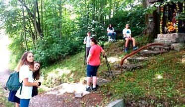 Grupa osób nagrywa materiał w plenerze.