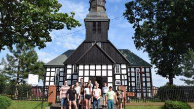Grupa pozuje do zdjęcia przed kościołem