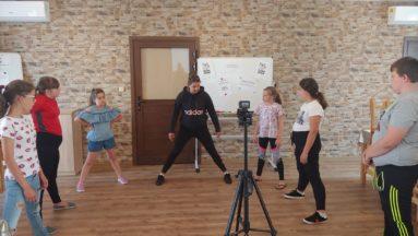 Na zdjęciu widzimy grupę dzieci i instruktorkę podczas zajęć sportowych. Na środku sali stoi aparat na statywie, za pomocą którego nagrywane są zajęcia.