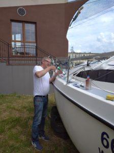 Na zdjęciu widać osobę wplenerze, pracującą nadodnowieniem jachtu.