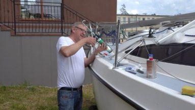 Na zdjęciu widać osobę w plenerze, pracującą nad odnowieniem jachtu.