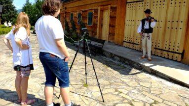 Dwie osoby nagrywają ubranego w ludowy strój mężczyznę.