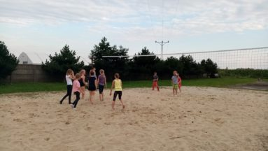 Dzieci grają w siatkówkę w plenerze