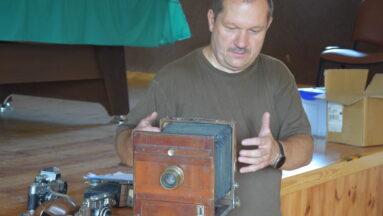 Na zdjęciu pan Ireneusz pokazuje jeden ze starych aparatów.