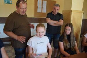 Na zdjęciu pan Ireneusz wraz zgrupą młodzieży przeglądają wykonane przeznich zdjęcia