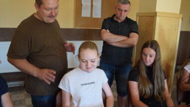 Na zdjęciu pan Ireneusz wraz z grupą młodzieży przeglądają wykonane przez nich zdjęcia
