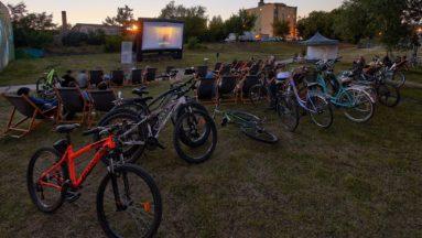 Zdjęcie przedstawia kino plenerowe - widownia siedzi na leżakach, a obok stoją ich rowery.