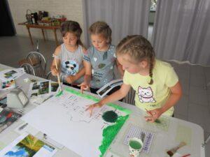 Dzieci malujące nakartce podczas warsztatów