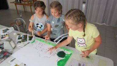 Dzieci malujące na kartce podczas warsztatów