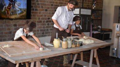 Pracownicy muzeum wraz z dziećmi przygotowują rogale